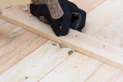 Работник бьет ноготь молотком в древесину стоковые изображения