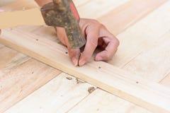 Работник бьет ноготь молотком в древесину стоковая фотография rf