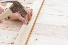 Работник бьет ноготь молотком в древесину стоковая фотография