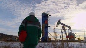 Работник взгляда задней стороны идет вдоль месторождения нефти с колодцем и деррик-краном сток-видео