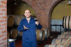 Работник винодельни с бокалом вина в погребе Стоковые Изображения RF