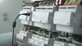 Работник включает кабель в электрическом шкафе акции видеоматериалы