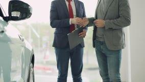 Работник выставочного зала мотора дает ключ автомобиля к молодому мужскому покупателю и трясущ руки, торговец держит документы и сток-видео