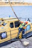 Работник вытягивая грузоподъемную цепь Стоковое Фото