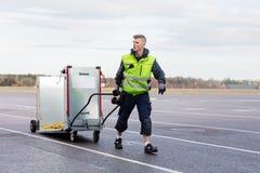 Работник вытягивая машину на тележке на взлётно-посадочная дорожка авиапорта Стоковые Фотографии RF