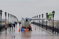 Работник в ведре на высоте красит фонарик на мосте ` s патриарх в Москве стоковые фото