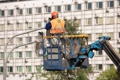 Работник в ведре подъема во время установки поляка металла с уличным фонарем, фонарным столбом улицы с двойной головой стоковые фотографии rf