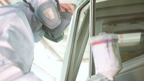 Работник в защитных форме и маске красит кабину тележки сток-видео