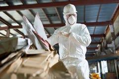 Работник в костюме Hazmat сортируя картон на заводе по переработке вторичного сырья стоковые фото
