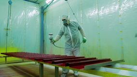Работник в красильной мастерской красит части с краской для пульвериз