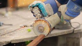 Работник в перчатках режа угловую машину трубы металла, конец вверх сток-видео