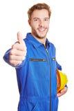 Работник в прозодежде держа большие пальцы руки вверх Стоковое Фото