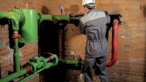 Работник в прозодеждах раскрывает клапан воды водопроводчик приходит и раскрывает клапан Человек включает топление в боилере сток-видео