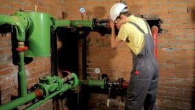 Работник в прозодеждах раскрывает клапан воды Человек включает топление в котельной акции видеоматериалы