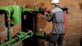 Работник в прозодеждах раскрывает клапан воды Человек включает топление в котельной видеоматериал