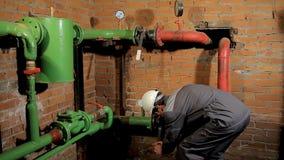 Работник в прозодеждах раскрывает клапан воды Человек включает топление в котельной сток-видео