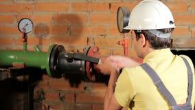 Работник в прозодеждах раскрывает клапан воды Человек включает топление в котельной Конец-вверх акции видеоматериалы