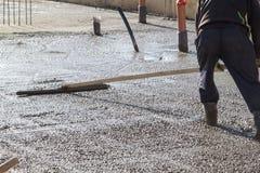 работник в резиновых ботинках стоит в uncluttered цементе и выравнивать стоковые фото