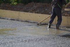 работник в резиновых ботинках стоит в uncluttered цементе и выравнивать стоковые изображения rf