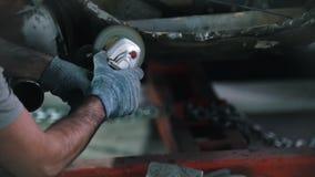 Работник в стеклах мелет отрезок на задней части автомобиля Ремонтные услуги автомобиля снимая искры сток-видео