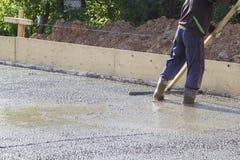 работник в стойках резиновых ботинок в uncluttered цементе и выравнивать стоковые изображения