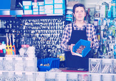Работник в товарах магазина оборудования торгуя для водопроводного крана в форме Стоковое Изображение RF