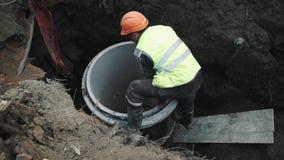 Работник в трудной шляпе кладет белизну на край конкретного кольца люка -лаза камеры в рев видеоматериал