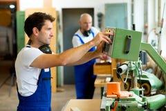 Работник в фабрике используя машину Стоковые Фотографии RF