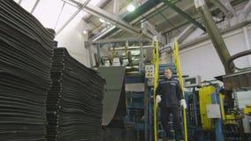 Работник в форме проверяет транспортер с резиной покрышки видеоматериал