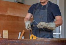 Работник в workwear сваривая стальную часть руководством с безопасностью стоковое фото