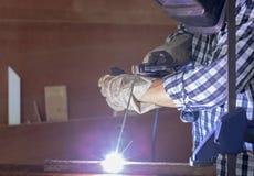 Работник в workwear сваривая стальную часть руководством с безопасностью стоковые изображения