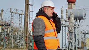 Работник говоря на сотовом телефоне на электростанции видеоматериал