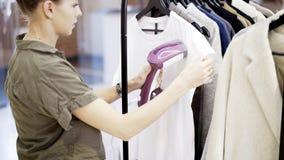 Работник девушки в магазине одежды испаряется одежды Стоковое Фото