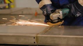Работник делает чистку поверхности металла Работа для защиты сваривая шва Конец-вверх рук и инструмента