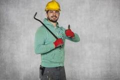 Работник держа лом в его руке, большом пальце руки вверх стоковые фотографии rf
