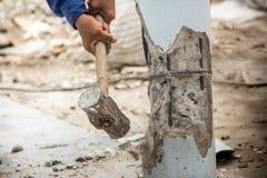 Работник держа молоток и огромный успех к бетону Стоковые Фото