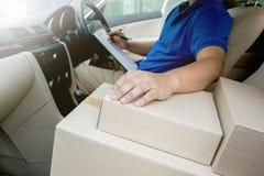 Работник доставляющий покупки на дом внутри контрольного списка автомобиля на доске сзажимом для бумаги стоковое изображение rf