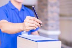 Работник доставляющий покупки на дом давая счет ручки и фактуры клиенту Концепция обслуживания доставки стоковые изображения