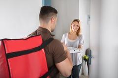 Работник доставляющий покупки на дом пиццы с большой красной сумкой Стоковая Фотография RF