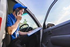 Работник доставляющий покупки на дом сидя на фургоне месте и вызывая к клиенту стоковое фото