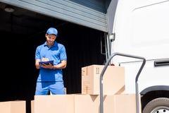 Работник доставляющий покупки на дом с доской сзажимом для бумаги Стоковое Фото