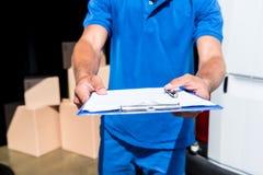 Работник доставляющий покупки на дом с доской сзажимом для бумаги Стоковая Фотография RF