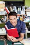 Работник держа красную книгу крышки в фабрике Стоковая Фотография RF