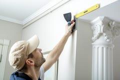 Работник держит нож замазки и измеряет угол стены используя угол металла Стоковые Фотографии RF