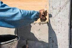 работник делает бетонную стену цементом преградить и заштукатурить на construc Стоковое Изображение RF