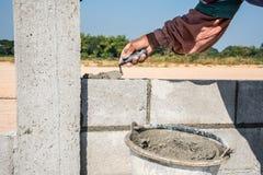 Работник делает бетонную стену цементом преградить и заштукатурить Стоковые Фотографии RF