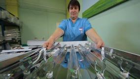Работник женщины в форме транспортирует стеклянные трубы лампы видеоматериал