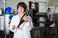 Работник женщины показывая бутылку вина Стоковое Изображение