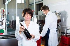 Работник женщины показывая бутылку вина Стоковые Фото