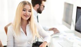 Работник женщины сидя на столе в офисе Стоковые Изображения